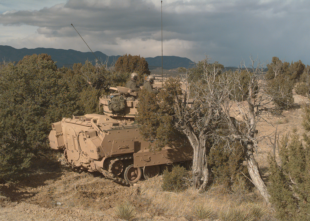 The crew of a Bradley Fighting Vehicle wait among the pinon pine and scrub oak trees of one of the many training sites. Colorado's Front Range and storm clouds loom in the background