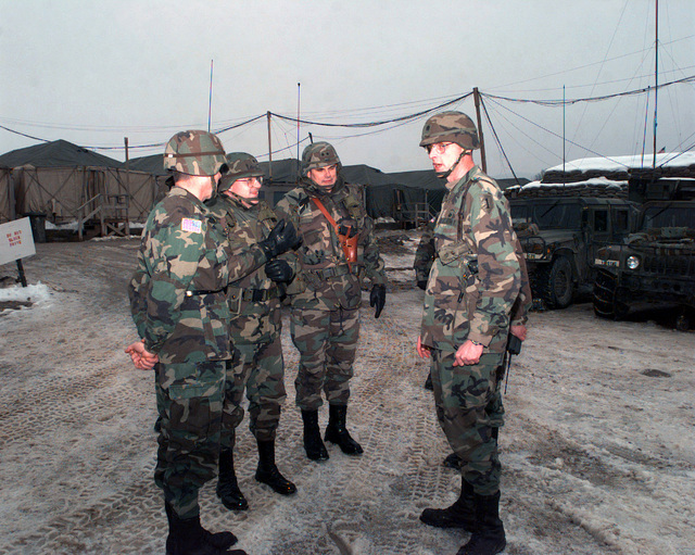 Major General [MGEN] Michitish, Program Executive Officer for Ground Combat and Support Systems, meets with (l-r) Colonel Thompson, MGEN Michitish, MG Montgomery C. Meigs, Lieutenant Colonel Robin Swan, during his visit to Camp Dobol, Bosnia-Herzegovina, during Operation JOINT GUARD. On December 20, 1996, the Implementation Force (IFOR) mission came to a conclusion and the 1ST Infantry Division was selected to continue serving in Bosnia as part of the new Stabilization Force (SFOR). This decision brought to close the peace mission of Operation JOINT ENDEAVOR and has been the beginning for the current operation known as Operation JOINT GUARD. JOINT GUARD will continue to monitor the...