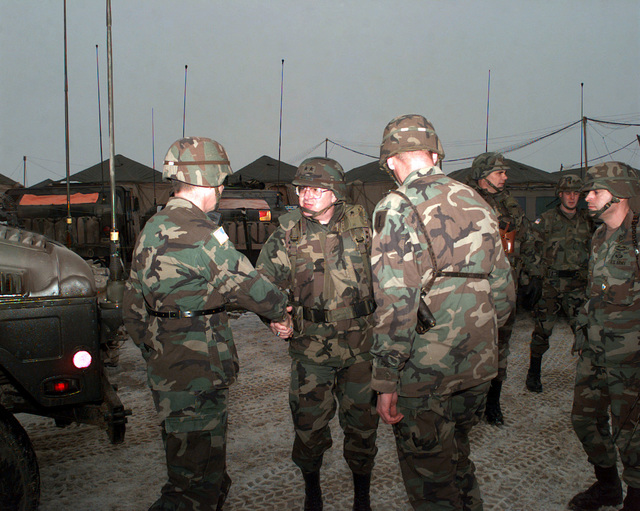 Major General Michitish, Program Executive Officer for Ground Combat and Support Systems, shakes hands with Colonel Thompson, First Infantry Commander, during his visit to Camp Dobol, Bosnia-Herzegovina, during Operation JOINT GUARD. On December 20, 1996, the Implementation Force (IFOR) mission came to a conusion and the 1ST Infantry Division was selected to continue serving in Bosnia as part of the new Stabilization Force (SFOR). This decision brought to ose the peace mission of Operation JOINT ENDEAVOR and has been the beginning for the current operation known as Operation JOINT GUARD. JOINT GUARD will continue to monitor the militaries of the former warring factions and provide a...