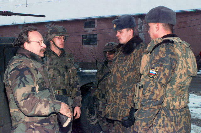 Russian soldiers and US Army First Lieutenant Wasser from Camp Dobol (Headquarters, Headquarters Command TF1-26 Sout Platoon) disuss the 'Joint Patrol' routes in the town of Karakaj, Bosnia-Herzegovina, during Operation JOINT GUARD. On Deember 20, 1996, the Implementation Fore (IFOR) mission ame to a onlusion and the 1ST Infantry Division was seleted to ontinue serving in Bosnia as part of the new Stabilization Fore (SFOR). This deision brought to lose the peae mission of Operation JOINT ENDEAVOR and has been the beginning for the urrent operation known as Operation JOINT GUARD. JOINT GUARD will ontinue to monitor the militaries of the former warring fations and provide a...