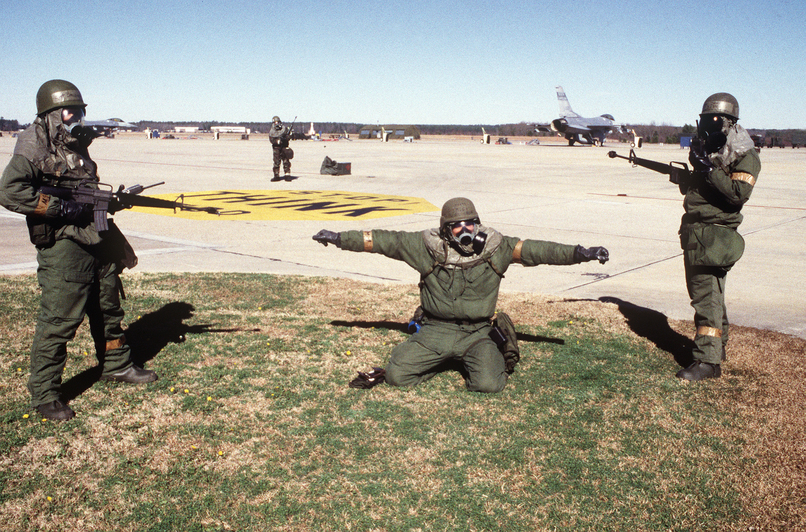 Two Security Police augmentees of the 169th Fighter Wing point their M-16 rifles at their kneeling intruder. They are on the flight line in Condition Black of an Operation Readiness Exercise. They all wear protective chemical warfare suits