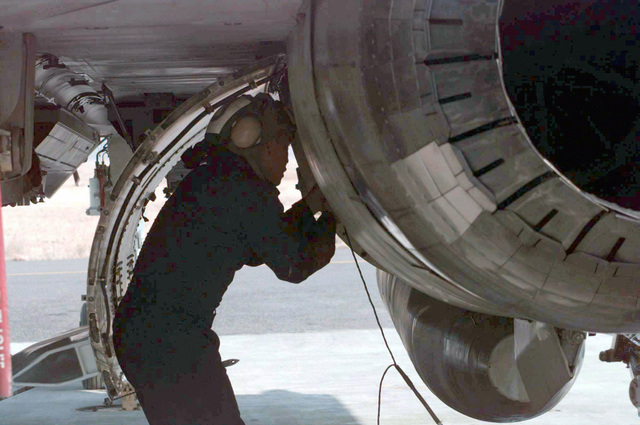 A maintenance crewmember from VF-154 performs routine checks on the jet engine of an F-14A Tomcat before start up at NAF Atsugi, Japan. Naval Air Station (NAS) at Atsugi was officially activated on April 1, 1943. On 1 July, 1971, NAS Atsugi was re-designated a Naval Air Facility (NAF) and began operating under a Joint Use agreement with the Japan Maritime Self Defense Force (JMSDDF). (Substandard image)