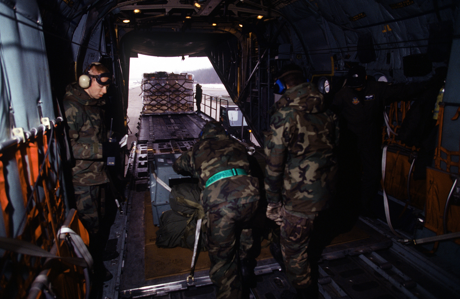 AIRMAN of the Mobility Unit at Tuzla push cargo pallets off the 40th Airlift Squadron (AS), C-130H Hercules aircraft after it's arrival at the former Yugoslavian air base. The 40th AS is assigned to the 7th Wing, Dyess Air Force Base, Texas and is deployed to Ramstein for a 45 day Temporary Duty (TDY) tour to support Operations Joint Endeavor