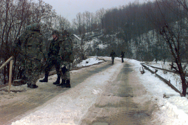 Six US Army soldiers walking on and standing near a snow-covered outside of Celic, Bosnia-Herzegovina. These soldiers are in Bosnia during Operation Joint Endeavor, which is a peacekeeping effort by a multinational Implementation Force (IFOR), comprised of NATO and non-NATO military forces, deployed to Bosnia in support of the Dayton Peace Accords