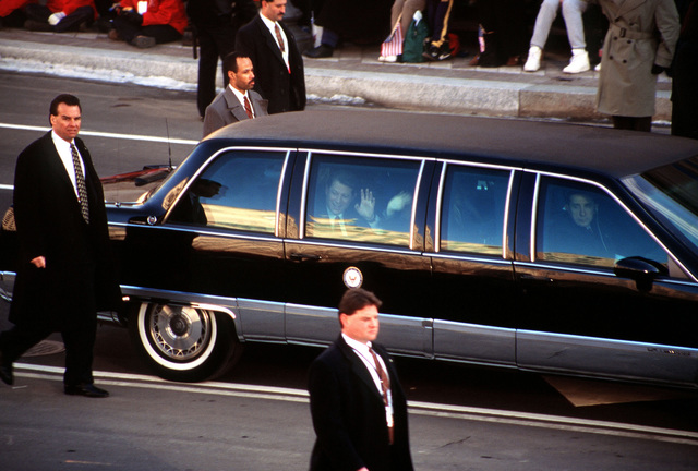 A close up view the Presidential Limousine carrying Vice President Al Gore and family, being escorted by members of the Secret Service as it travels along the parade route during the 1997 Presidential Inaugural Parade