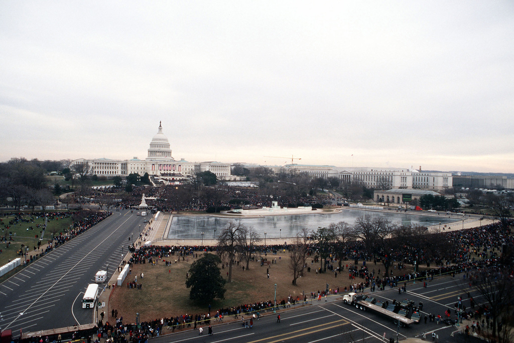 An extreme long shot wide angel view showing the US Capitol Building taken near the intersection of 3RD and Pennsylvania Avenue NW, with the Capitol Reflecting Pool in the middle ground and the Federal Office Buildings in the Foreground, surrounded by crowds of spectators and visitors during the 1997 Presidential Inauguration