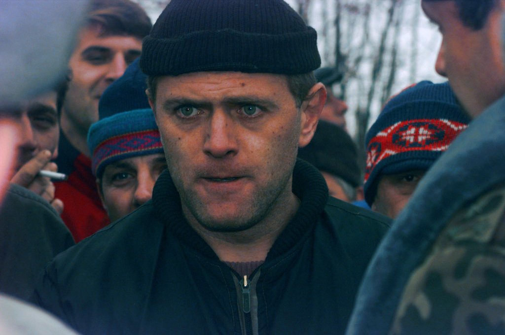 A close up of a Serbian resident from the town of Gajevi, Bosnia-Herzegovina as he stares between Russian Soldiers guarding Muslim refugees returning to the town for resettlement