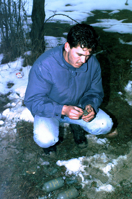 A Bosnian Muslim civilian works at reattaching the safety pin to the firing mechanism of a PROM-1 Bouncing (Bouncing Betty style) Anti-personnel Mine, two more PROM-1 mines lie on the snow-covered ground, that was found by other Muslims during their village rebuilding efforts in Celic, Bosnia-Herzegovina