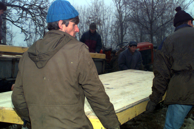 Muslim residents unload prefabricated building material from a small trailer near the town of Celic, Bosnia-Herzegovina, during the rebuilding and resettlement process