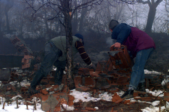 Two Muslim residents work hard to clear debris from a destroyed house in the town of Celic, Bosnia-Herzegovina, during the rebuilding and resettlement process