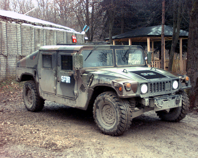 A M998 High-Mobility Multipurpose Wheeled Vehicle (HMMWV) (M1043 varrient) vehicle awaits it's driver at Tuzla Air Base. This all terrain vehicle is perfect for the road conditions that typically confront the personnel assigned here in support of Operation JOINT GUARD. On December 20, 1996, the Implementation Force (IFOR) mission came to a conclusion and the 1ST Infantry Division was selected to continue serving in Bosnia as part of the new Stabilization Force (SFOR). This decision brought to close the peace mission of Operation JOINT ENDEAVOR and has been the beginning for the current operation known as Operation JOINT GUARD. JOINT GUARD will continue to monitor the militaries of the...