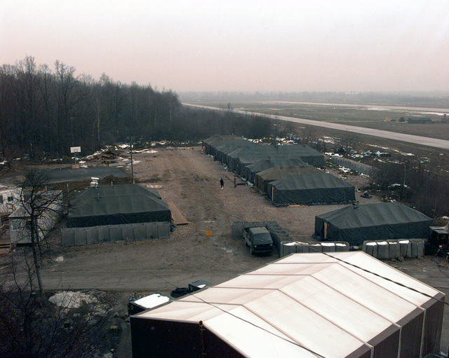 A view of the flightline, taxiway and one of the tent complexes for Air Force personnel assigned here, taken from the air traffic control tower of Tuzla Air Force Base. This main staging area for the airlift of supplies and equipment in support of Operation T GUARD is eight kilometers (five miles) from one of the task force boundaries. On December 20, 1996, the Implementation Force (IFOR) mission came to a conclusion and the 1ST Infantry Division was selected to continue serving in Bosnia as part of the new Stabilization Force (SFOR). This decision brought to close the peace mission of Operation T ENDEAVOR and has been the beginning for the current operation known as Operation...