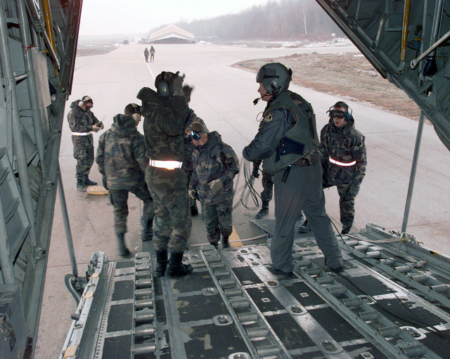 "Members from ""Team Tuzla"" greet a C-130 Hercules transport aircraft arriving to Tulza Air Base from Ramstein Air Base Germany in support of Operation JOINT GUARD. C-130 aircraft are used for most of the arriving supplies into Tuzla. Personnel that support the aircraft meet an arriving aircraft within five seconds. The complete offload takes well under thirty minutes. On December 20, 1996, the Implementation Force (IFOR) mission came to a conclusion and the 1ST Infantry Division was selected to continue serving in Bosnia as part of the new Stabilization Force (SFOR). This decision brought to close the peace mission of Operation JOINT ENDEAVOR and has been the beginning for the current..."