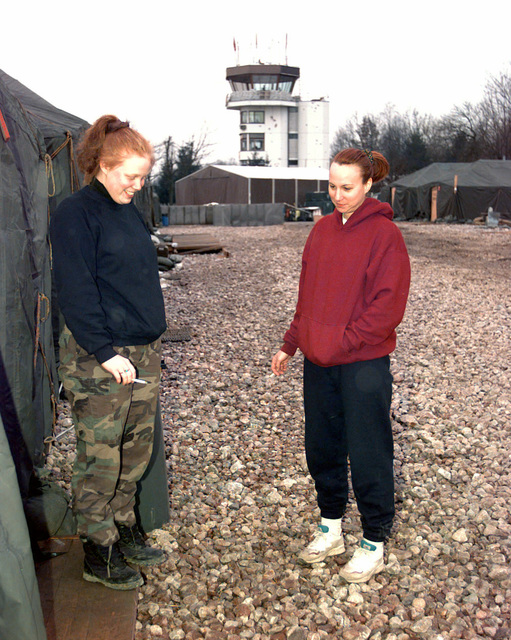 """SENIOR AIRMAN Cathy A. Bjork and SENIOR AIRMAN Rachael K. Hawkins both from 48th Security Police Squadron, Royal Air Force Base Lakenheath, talk about ir last work shift and unwind during continuing operations in support of Operation JOINT GUARD. These """"Peacekeepers"""" ensure that all operations continue without threat of hostilities for those personnel assigned at Tuzla. On December 20, 1996, Implementation Force (IFOR) mission came to a conclusion and 1ST Infantry Division was selected to continue serving in Bosnia as part of new Stabilization Force (SFOR). This decision brought to close peace mission of Operation JOINT ENDEAVOR and has been beginning for..."""