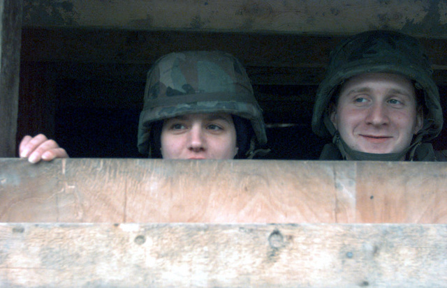 """Two Airmen First Class, both from the 48th Security Police Squadron, Royal Air Force Base Lakenheath, stand guard at one of several entry control points at Tuzla Air Base in support of Operation JOINT ARD. These """"Peacekeepers"""" ensure that all operations continue without the threat of hostilities for those personnel assigned at Tuzla. On December 20, 1996, the Implementation Force (IFOR) mission came to a conclusion and the 1ST Infantry Division was selected to continue serving in Bosnia as part of the new Stabilization Force (SFOR). This decision brought to close the peace mission of Operation JOINT ENDEAVOR and has been the beginning for the current operation known as Operation JOINT..."""