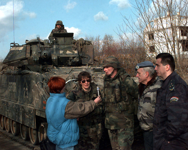 LTC Robin Swan (USA), TF1-26 Batallion Commander and wearing the helmet, Charlie Hayes, International Police Task Force (IPTF), and CHIEF Vosic, CHIEF of Police for Zvornik, Bosnia-Herzegovina, standing in front of an SFOR marked US Army M2A2 Bradley Infantry fighting Vehicle (IFV), are interviewed by a local reporter after touring Mahala, Bosnia-Herzegovina. These individuals toured Mahala in preparation of resettling Bosnia Muslims in to this village, during Operation Pollux, which is part of Operation Joint Guard, which is part of Operation Joint Endeavor. Operation Joint Endeavor is a peacekeeping effort by a multinational Implementation Force (IFOR), comprised of NATO and non-NATO...