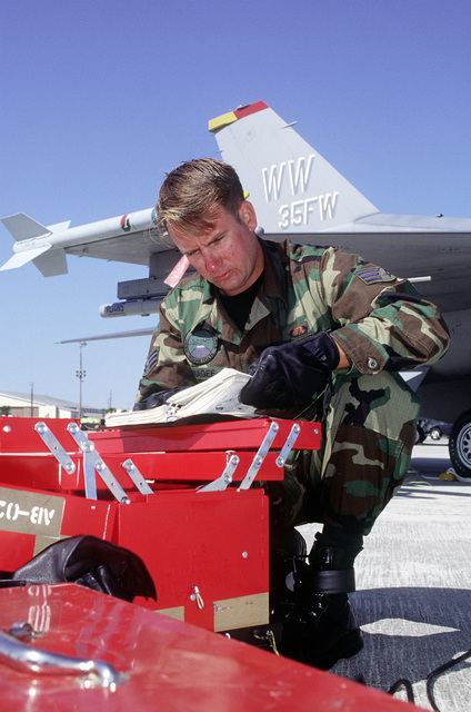 SENIOR AIRMAN Kenneth Magee, 35th Fighter Wing, Misawa Air Base, Japan, (PACAF) on the flight line, next to one of the 35th FW's F-16 Fighting Falcon, reviews tech orders before performing aircraft maintenance for WILLIAM TELL '96, 23 - 25 October 1996. Held biennially at Tyndall Air Force Base, Fla., and conducted by Air Combat Command, WILLIAM TELL '96 pushes fighter units, including those from Canada, to achieve air superiority under combat conditions, to intercept and destroy enemy jets. And it assesses tactics and weapons and fine-tunes air and ground crews