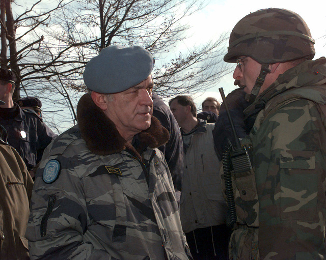 US Army Lieutenant Colonel Robin Swan, TASK FORCE [TF] 1-26 Batallion Commander, talks with Charlie Hayes, CHIEF of International Police Task Force Zvornik, in the village of Mahala during the resettlement of Muslims (Operation POLLUX) in Mahala, Bosnia-Herzegovina, during Operation JOINT GUARD. On December 20, 1996, the Implementation Force (IFOR) mission came to a conclusion and the 1ST Infantry Division was selected to continue serving in Bosnia as part of the new Stabilization Force (SFOR). This decision brought to close the peace mission of Operation JOINT ENDEAVOR and has been the beginning for the current operation known as Operation JOINT GUARD. JOINT GUARD will continue to...