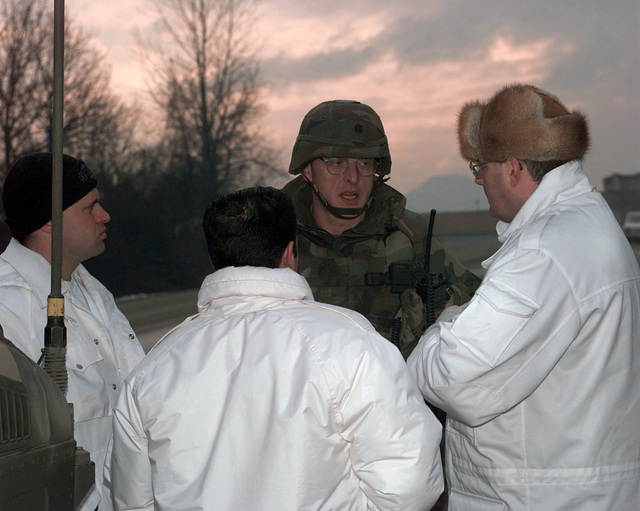 US Army Lieutenant Colonel Robin Swan, Task Force [TF] 1-26 Batallion Commander, meets with members of the European Community Monitoring Mission before the resettlement of Muslims (Operation POLLUX) in Mahala, Bosnia-Herzegovina, during Operation JOINT GUARD. On December 20, 1996, the Implementation Force (IFOR) mission came to a conclusion and the 1ST Infantry Division was selected to continue serving in Bosnia as part of the new Stabilization Force (SFOR). This decision brought to close the peace mission of Operation JOINT ENDEAVOR and has been the beginning for the current operation known as Operation JOINT GUARD. JOINT GUARD will continue to monitor the militaries of the former...