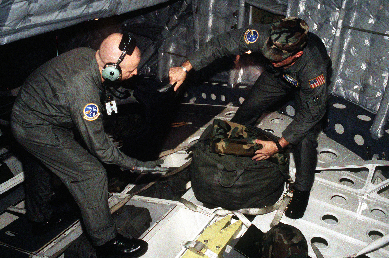 STAFF SGT. William E. Pace (right) and STAFF SGT. Brian D. McGriff, loadmasters with the 14th Airlift Squadron (AS), pull flak jackets and associated equipment from holds in the rear of the C-17 Globemaster III. Once in Bosnian airspace, all crewmembers are required to don a protective flak vest and helmet. The 14th AS's C-17s assigned to the 437th Airlift Wing, Charleston Air Force Base, S.C. are providing inter-theater transport capability to the former Yugoslavia region in support the United Nation's Implementation Force
