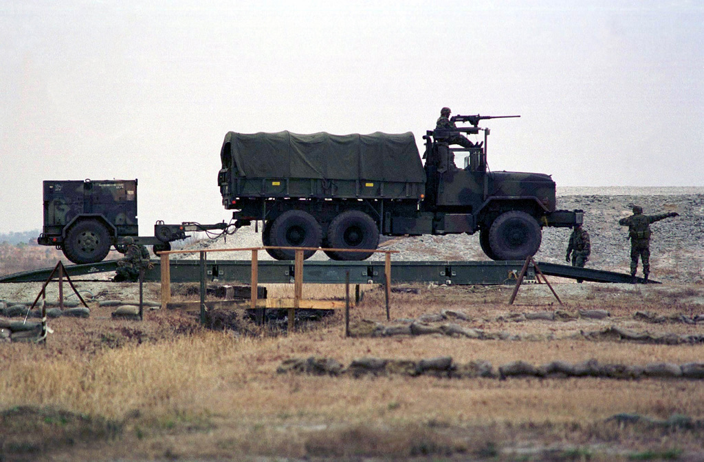 A M-939A2 5 ton truck armed with a M-2 .50 Calibar Medium Machine Gun, towing a MEP-006 generator, heads across a Medium Girder Bridge at OP-5, Camp Lejeune, North Carolina. This truck was part of a convoy of vehicles simulating a mobile CSSD (Combat Service Support Detachment) rehearsing for a demonstration that would be given the following day as part of the REVISED CAPABILITIES Exercise