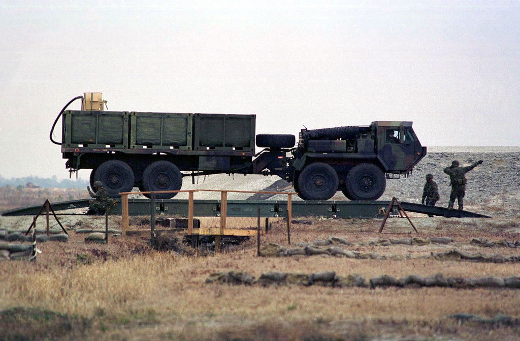 A MK48/14 LVS (Logistics Vehicle System) heads across a Medium Girder Bridge at OP-5, Camp Lejeune, North Carolina. This truck was part of a convoy of vehicles simulating a mobile CSSD (Combat Service Support Detachment) rehearsing for a demonstration that would be given the following day as part of the REVISED CAPABILITIES Exercise