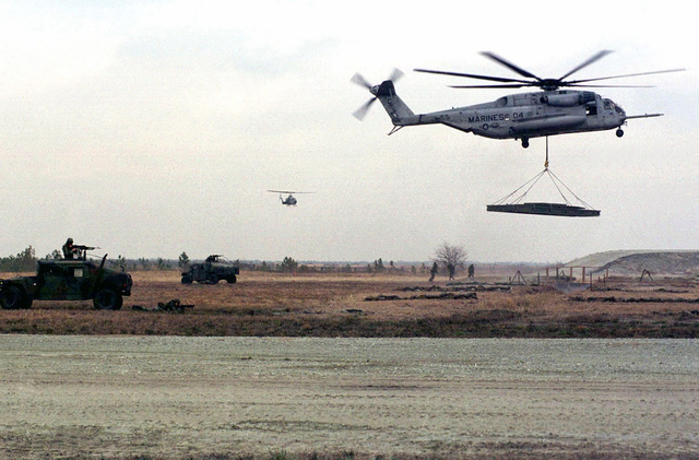 """Military Police and an AH-1w Cobra helicopter provide cover while a HST (Helicopter Support Team) from 2d FSSG (Force Service Support Group) guides in a CH-53E Super Stallion helicopter carrying a Medium Girder Bridge to replace one previously """"blown up"""" by the enemy, at OP-5, Camp Lejeune, NC. These Marines were rehearsing for a demonstration that would be given the following day as part of the REVISED CAPABILITIES Exercise"""