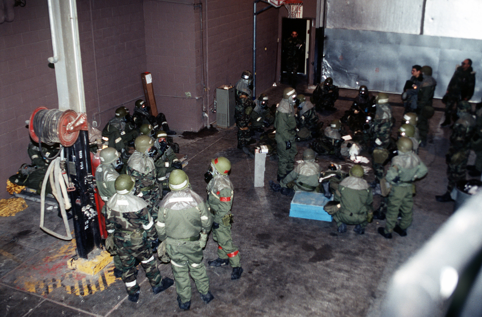 Participants wearing full chemical warfare gear wait in a secure building during the Operation Readiness Exercise