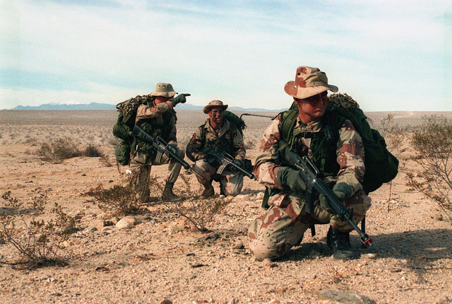 """STAFF Sergeant Paul D. Lusk, 1ST Squad Leader, 2nd platoon, Kilo Co, 3/4 (3rd Battalion, 4th Marines), gives instuctions to radio operator, Private First Class (PFC) John M. Keane, while conducting a sensor emplacement mission. PFC Joshua E. Remmert (foreground) provides security. The three Marines are part of a Hunter-Killer team participating in the Advanced Warfighting Experiment, """"Hunter-Warrior"""", held at MCAGCC (Marine Corps Air Ground Combat Center) 29 Palms, California"""