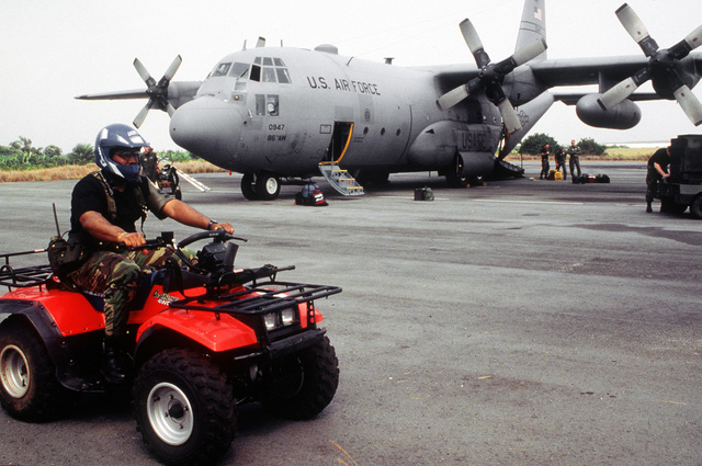 SRA Robert G. Palmer, a security policeman from the 86th Security Police Squadron, Ramstein Air Base, Germany, rides on an ATV (all terrain vehicle) providing security for a C-130E aircraft from the 86th Airlift Wing arriving at Abidjan Felix/Houphouet/Boigny International Airport