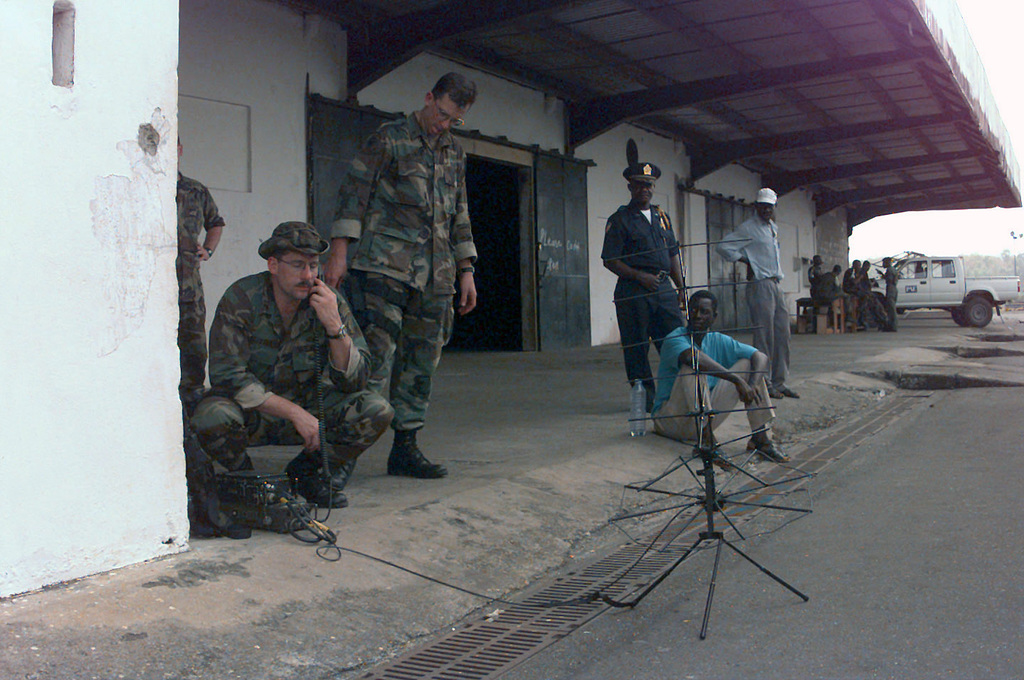 United States Army STAFF Sergeant Steve G. Tuttle (left) and STAFF Sergeant William S. Collins (right) from 3rd Special Forces Group, 1ST Battalion, out of Fort Bragg, North Carolina, communicate with the Joint Task Force (JTF) personnel at Abidjan Felix/Houphouet/Boigny International Airport in Cote D' Ivoire (Ivory Coast) with a Tactical Satellite Communication Radio (TACSAT) at Roberts International Airport located outside of Monrovia, Liberia. The Special Forces Group will be providing security for United States Military aircraft landing in Liberia in support of Operation ASSURED LIFT. ASSURED LIFT is a Joint Task Force Operation to provide airlift and other logistical support to...
