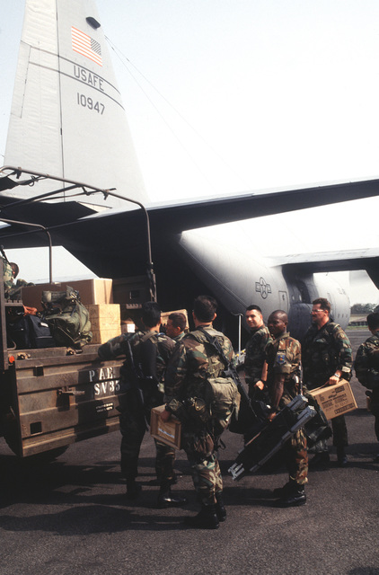 U.S. Army Special Forces from the 3rd Special Forces Group, 1ST Battalion, Fort Bragg, N.C., off load supplies and equipment from an 86th Air Wing, Ramstein AB, Germany C-130E Hercules at Robert's International Airport, located outside Monrovia, Liberia. The Special Forces Group will be providing security for U.S. military aircraft participating in Operation Assured Lift, a 17 day United States airlift and support mission assisting West African states deploying more than 1100 troops to Liberia as part of the region's ongoing peacekeeping force