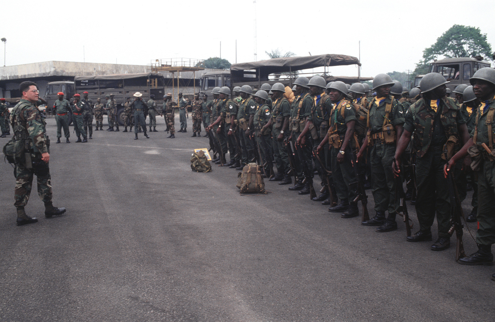 MASTER Sergeant Thomas A. Nelson (far left), from the 3rd Special Forces Group, 1ST Battalion, Fort Bragg, N.C., checks out the Economic Community Military Observation Group 13 (ECOMOG) Ghana Army troops in formation at Accra Airport Ghana. The troops are being airlifted to Robert's International Airport, Liberia for a six month deployment on U.S. military aircraft participating in Operation Assured Lift, a 17- day United States airlift and support mission assisting the West African states deploying more than 1100 troops to Liberia as part of the region's ongoing peacekeeping force