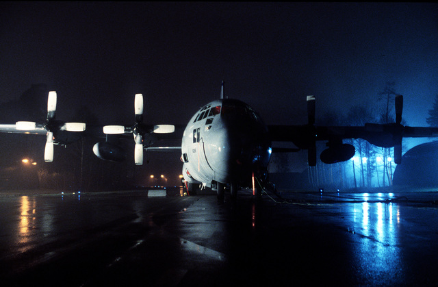 At night on a wet ramp, a 40th Airlift Squadron (AS) C-130H stands ready for operation at this United States Air Force Europe (USAFE) base. The 40th AS is assigned to the 7th Wing, Dyess Air Force Base, Texas and is deployed to Ramstein to support Operations Joint Endeavor and Joint Guard from 4 Dec. 1996 to 23 Jan. 1997