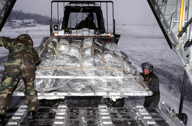 STAFF SGT. Christopher Rife, a C-130H loadmaster with the 40th Airlift Squadron (AS), assists with the uploading of a cargo pallet into the aircraft at the cold, snow-covered base. The 40th AS is assigned to the 7th Wing, Dyess Air Force Base, Texas and is deployed to Ramstein to support Operations Joint Endeavor and Joint Guard from 4 Dec. 1996 to 23 Jan. 1997