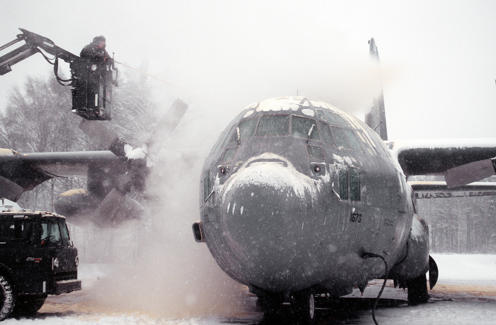 Working under frigid conditions, crew chief and ground support personnel de-ice a 40th Airlift Squadron (AS), C-130H taxies on the snow covered ramp at this United States Air Force Europe (USAFE) base. The 40th AS is assigned to the 7th Wing, Dyess Air Force Base, Texas and is deployed to Ramstein to support Operations Joint Endeavor and Joint Guard from 4 Dec. 1996 to 23 Jan. 1997.Exact Date Shot Unknown
