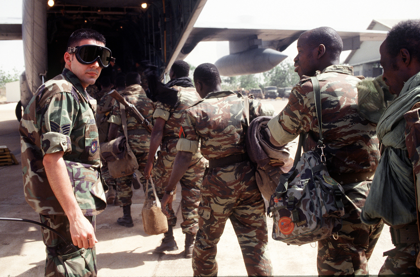 A U.S. Air Force STAFF Sergeant assists Mali Army troops from the Economic Community Military Observation Group 13 (ECOMOG) Mali Army troops as they board a U.S. Air Force C-130E from the 86th Airlift Wing, Ramstein Air Base, Germany at Bamako/Seou Airport, Mali. The troops are being airlifted to Robert's International Airport, Liberia for a six month deployment on U.S. military aircraft participating in Operation Assured Lift, a 17- day United States airlift and support mission assisting the West African states deploying more than 1100 troops to Liberia as part of the region's ongoing peacekeeping force