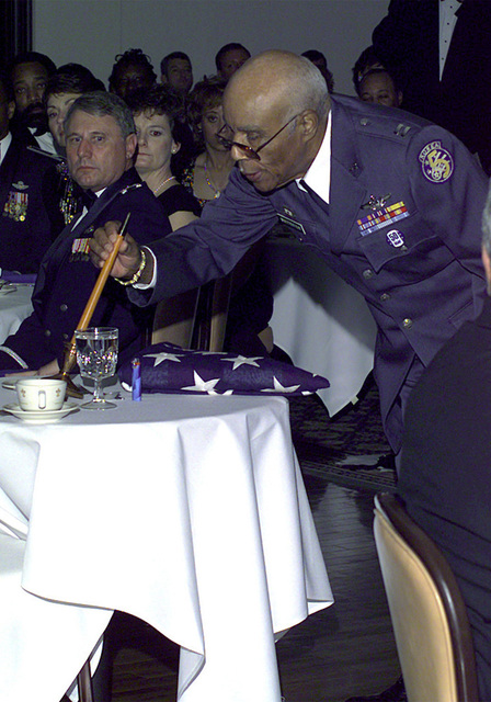 """Retired U.S. Air Force Captain Albert Whitesides Jr., 76, one of the original Tuskegee Airmen, blows out a candle during the """"Lonely Eagle"""" ceremony in the Randolph Officer's Club. About 20 pilots, original members of the famed black World War II flying unit, were in attendance for the ceremony which commemorated Tuskegee Airmen who are no longer living and also celebrated the 50th anniversary of the U.S. Air Force"""