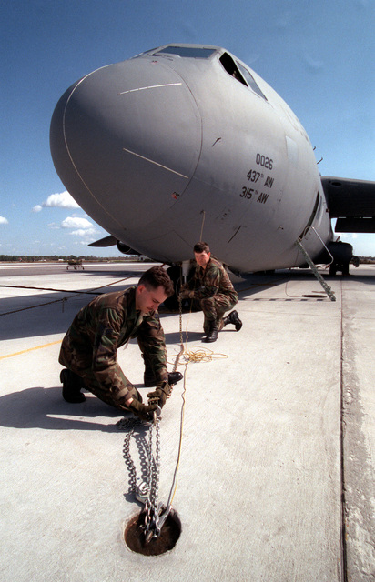 On the C-141 cargo aircraft flight line, SRA Chad E. Nixon (left) and SRA Sean Ames from the 437th Aircraft Generation Squadron adjust the tie down chains on one of the 437th Airlift Wing's C-141 Starlifter