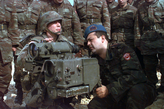 Captain Yakin, of the Turkish Artillery Brigade, out of Zenica, Bosnia, gets a bird's eye view through the Ground Vehicular Laser Locator Designator. Second Lieutenant Keith Jensen, of the 1/7th Artillery Battalion, explains to the rest of the Turkish soldiers how this piece of equipment works on their visit to Camp Dobol, Bosnia during Operation JOINT GUARD. On December 20, 1996, the Implementation Force (IFOR) mission came to a conclusion and the 1ST Infantry Division was selected to continue serving in Bosnia as part of the new Stabilization Force (SFOR). This decision brought to close the peace mission of Operation JOINT ENDEAVOR and has been the beginning for the current operation...