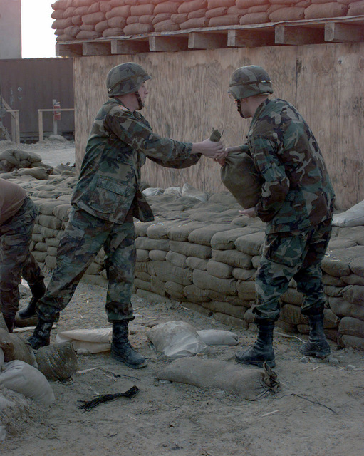 Soldiers of the 1/26 Task Force, out of Schweinfurt, Germany, pass off sand bags, as they are filled, at Camp Dobol, for the improvement of force protection while deployed to Bosnia during Operation JOINT GUARD. On December 20, 1996, the Implementation Force (IFOR) mission came to a conclusion and the 1ST Infantry Division was selected to continue serving in Bosnia as part of the new Stabilization Force (SFOR). This decision brought to close the peace mission of Operation JOINT ENDEAVOR and has been the beginning for the current operation known as Operation JOINT GUARD. JOINT GUARD will continue to monitor the militaries of the former warring factions and provide a climate of stability