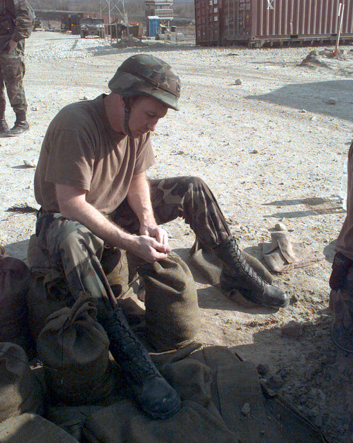 SPECIALIST First Class [SFC] Mark Andrews, of the 404th Civil Affairs Battalion, helps in tying sand bags for the improvement of force protection on Camp Dobol while deployed to Bosnia during Operation JOINT GUARD. On December 20, 1996, the Implementation Force (IFOR) mission came to a conclusion and the 1ST Infantry Division was selected to continue serving in Bosnia as part of the new Stabilization Force (SFOR). This decision brought to close the peace mission of Operation JOINT ENDEAVOR and has been the beginning for the current operation known as Operation JOINT GUARD. JOINT GUARD will continue to monitor the militaries of the former warring factions and provide a climate of stability