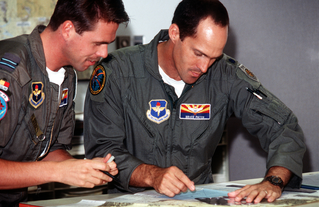 Lieutenant Colonel Bruce Patch, 162nd Fighter Wing, F-16 Instructor pilot, reviews flight information with a Belgium student during a preflight briefing