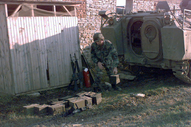 STAFF Sergeant Duncan, from the Explosives Ordnance Detachment, carefully retrieves cases of .50 caliber rounds from a YRP-765 Armored Personnel Carrier that had been seized, by SFOR, in a weapons storage site in the town of Karakaj, Bosnia, and brought to Camp Dobol during Operation JOINT GUARD. On December 20, 1996, the Implementation Force (IFOR) mission came to a conclusion and the 1ST Infantry Division was selected to continue serving in Bosnia as part of the new Stabilization Force (SFOR). This decision brought to close the peace mission of Operation JOINT ENDEAVOR and has been the beginning for the current operation known as Operation JOINT GUARD. JOINT GUARD will continue to...