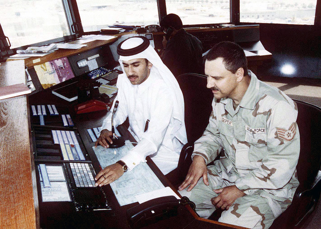US Air Force STAFF Sergeant Mike Cooper works with Qatar Air Traffic Controller Mohamed Al-Asmakh in the control tower at Doha, Qatar, during Operation SOUTHERN WATCH. Both controllers learn from one another and have mutual respect for each other's job knowledge. SOUTHERN WATCH enforces the United Nations Security Council Resolution 688 that establishes a no-fly zone over Southern Iraq below the 32nd parallel