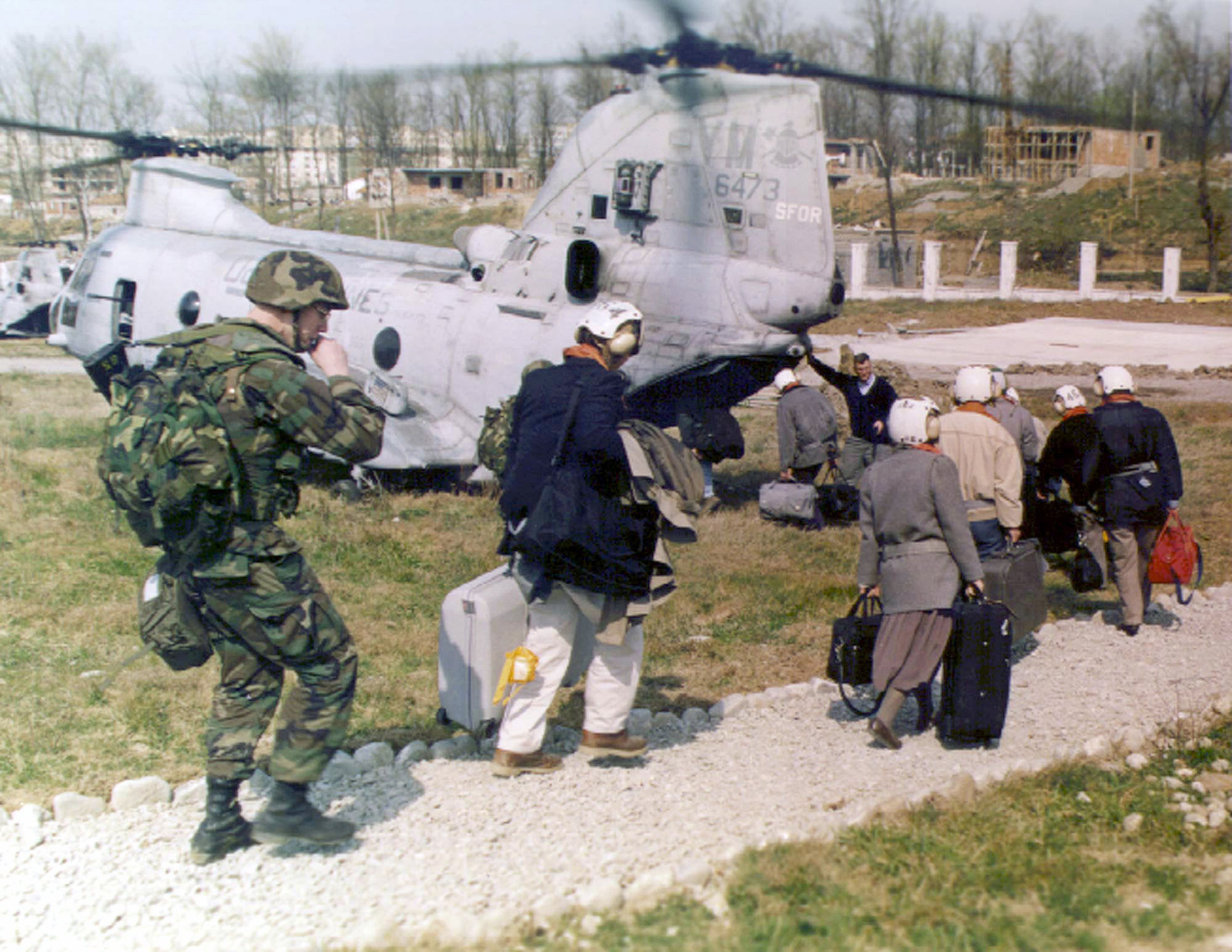 """American citizens are escorted to a CH-46E """"Sea Knight"""" helicopter by a 26th Marine Expeditionary Unit (Special Operations Capable) (MEU(SOC)) Marine, during Operation SILVER WAKE. 26th MEU (SOC) was called upon to perform a NEO (Non-combatant Evacuation Operation) of US citizens that desired to leave Albania, due to the current civil strife"""