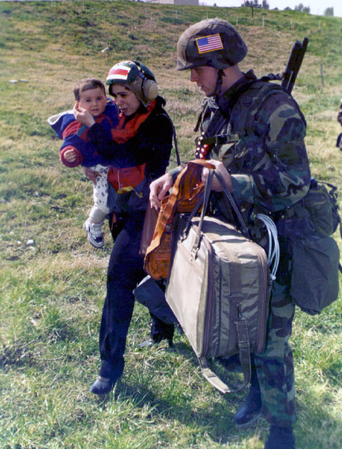 Sergeant David Smith, a Military Policeman assigned to the 26th MEU (SOC) (Marine Expeditionary Unit (Special Operations Capable)), escorts a woman and her child towards a waiting helicopter during Operation SILVER WAKE. 26th MEU (SOC) was called upon to perform a NEO (Non-combatant Evacuation Operation) of US citizens that desired to leave Albania, due to the current civil strife