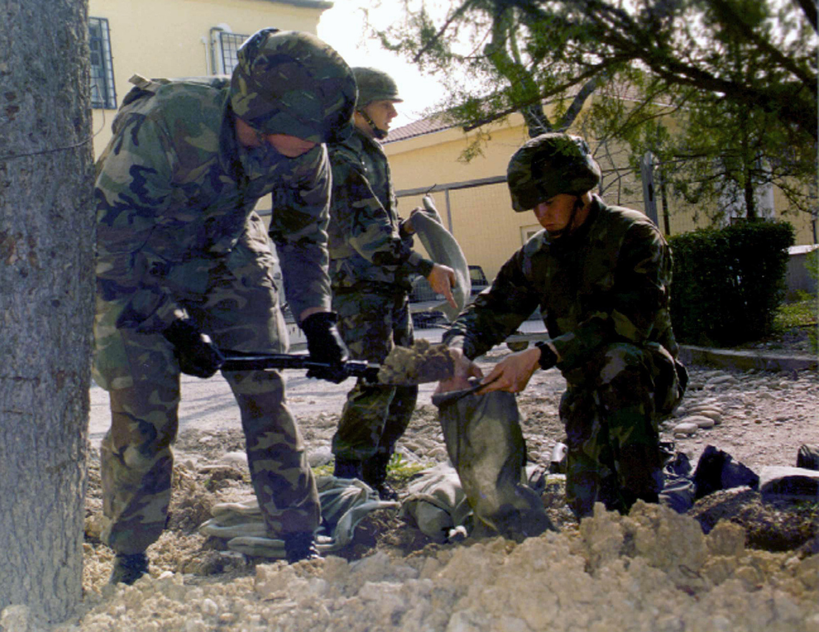 Marines from Charlie Company, 1ST Batttalion, 8th Marines, fill sandbags to reinforce defensive positions inside the compound at the US Embassy in Tirana, Albania, during Operation SILVER WAKE. The 26th Marine Expeditionary Unit (Special Operations Capable) (MEU (SOC)) was called upon to perform a NEO (Non-combatant Evacuation Operation) of US citizens that desired to leave Albania, due to the current civil strife