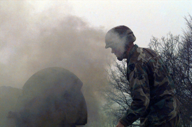 STAFF Sergeant David Duncan, from the Explosive Ordnance Detachment, currently attached to 1/26 Task Force, attempts to assess the situation moments after the initial blast of the T55 Russian tank in the field artillery area of operation on Camp Dobol, Bosnia, during Operation Operation JOINT GUARD. On December 20, 1996, the Implementation Force (IFOR) mission came to a conclusion and the 1ST Infantry Division was selected to continue serving in Bosnia as part of the new Stabilization Force (SFOR). This decision brought to close the peace mission of Operation JOINT ENDEAVOR and has been the beginning for the current operation known as Operation JOINT GUARD. JOINT GUARD will continue to...