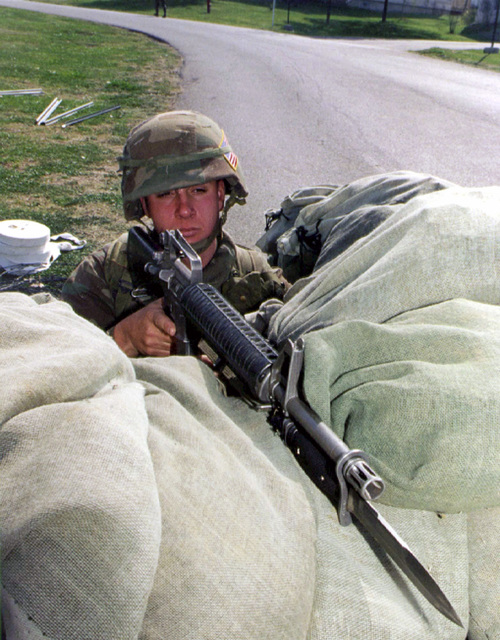 """Corporal Nathan Church, 3rd Platoon, """"B"""" Co, Battalion Landing Team 1/8, 26th Marine Expeditionary Unit (Special Operations Capable) (MEU(SOC)), sits with fixed bayonet on his M16A2 assault rifle behind a sandbagged defense position in the US Embassy housing complex in Tirana, Albania, during Operation SILVER WAKE. The 26th MEU (SOC) was called upon to perform a NEO (Non-combatant Evacuation Operation) of US citizens that desired to leave Albania, due to the current civil strife"""